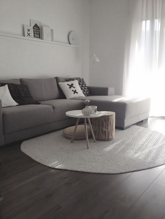 a small minimalist living room with a ledge gallery wall, a taupe sectional, a duo of coffee tables and printed pillows