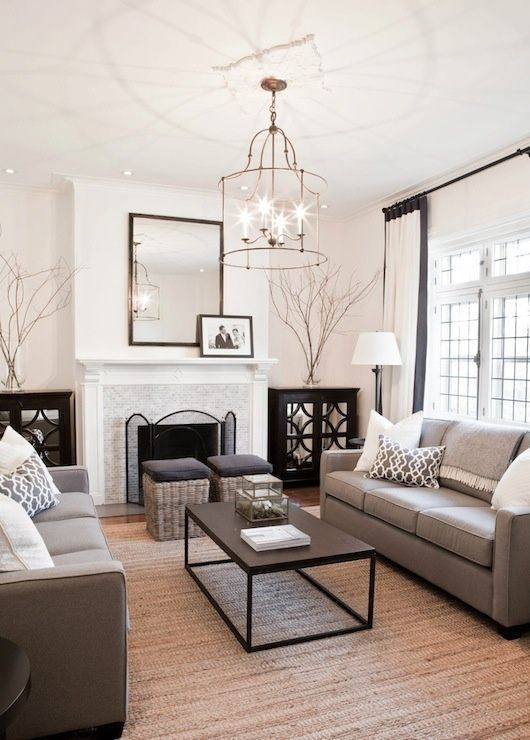 a traditional living room with taupe sofas, woven stools, creamy curtains and pillows, a chic chandelier and a non-working fireplace
