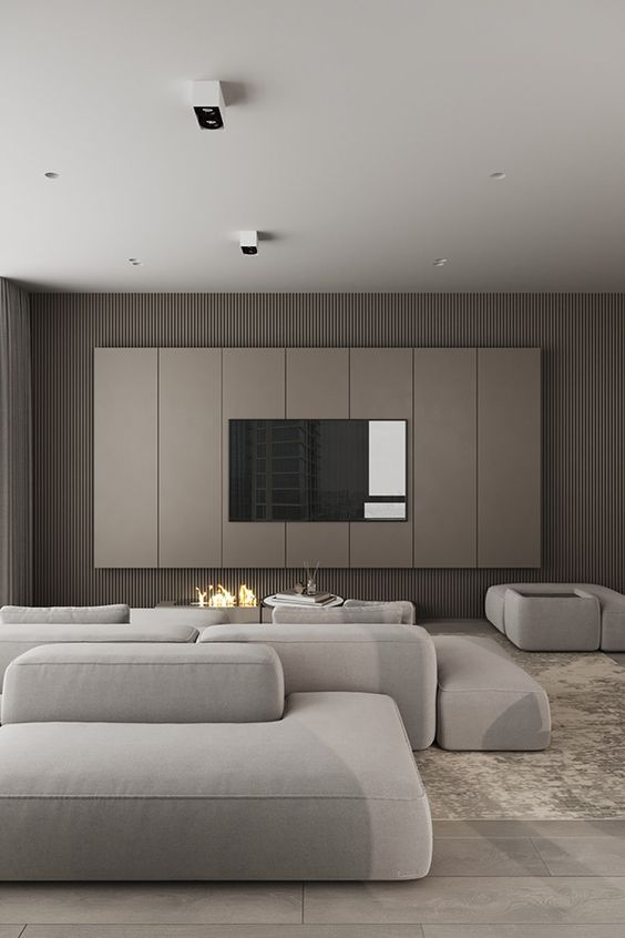 an ultra-minimalist living room with taupe wooden slab walls, a tan paneled accent with a TV, an open fireplace, neutral seating furniture