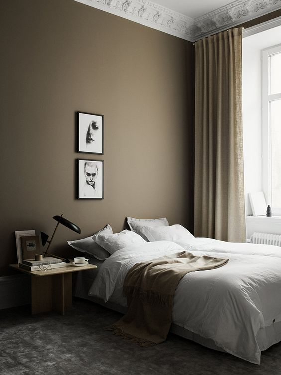 a beautiful Scandi bedroom with a taupe accent wall, a bed, a light-stained nightstand, a mini gallery wall and tan and gold touches