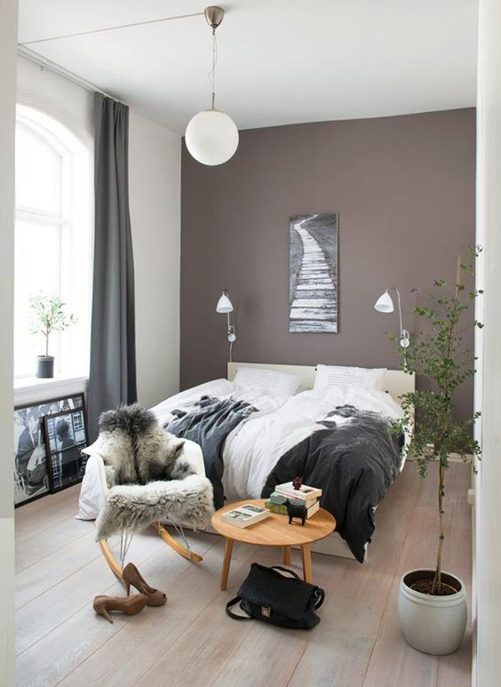 a beautiful boho bedroom with a taupe accent wall, a creamy upholstered bed and lovely bedding, a round table and a chair, a potted plant