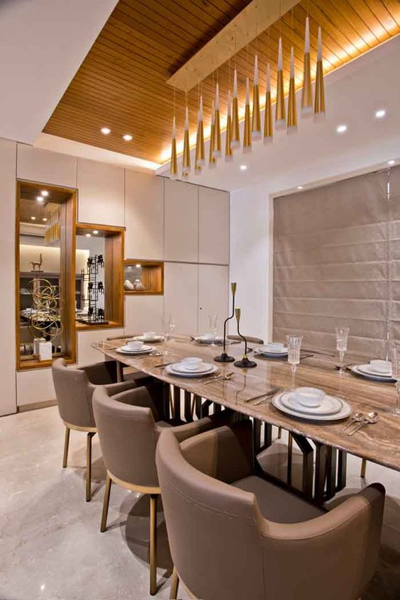 a beautiful contemporary dining room with built-in and pendant lamps, with a long table and taupe chairs, a storage unit with mirrors