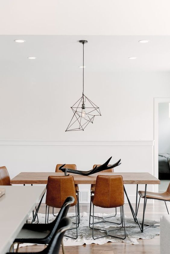 a beautiful contemporary dining space with a hairpin leg table, leather chairs, a catchy geometric pendant lamp is wow