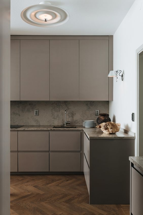 a beautiful taupe minimalist kitchen with taupe stone countertops and a backsplash, various lamps and built-in appliances is elegant