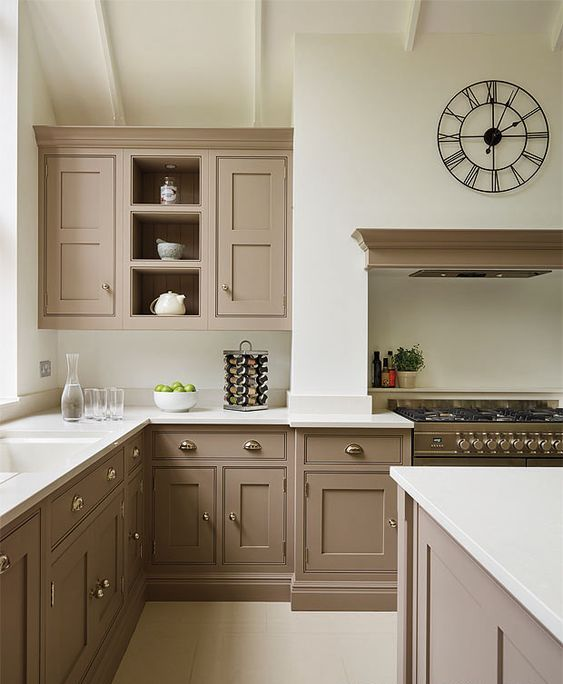 a beautiful taupe vintage kitchen with shaker cabinets, white countertops and a backsplash, a cooker with a hood, a catchy clock and vintage knobs