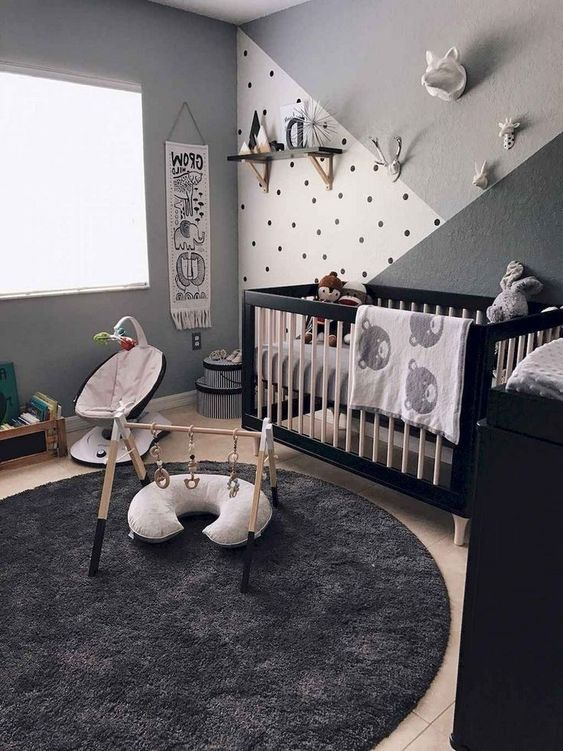 a black, grey and white nursery with a black and white crib, a black dresser, some baby furniture, shelves and toys is very cool