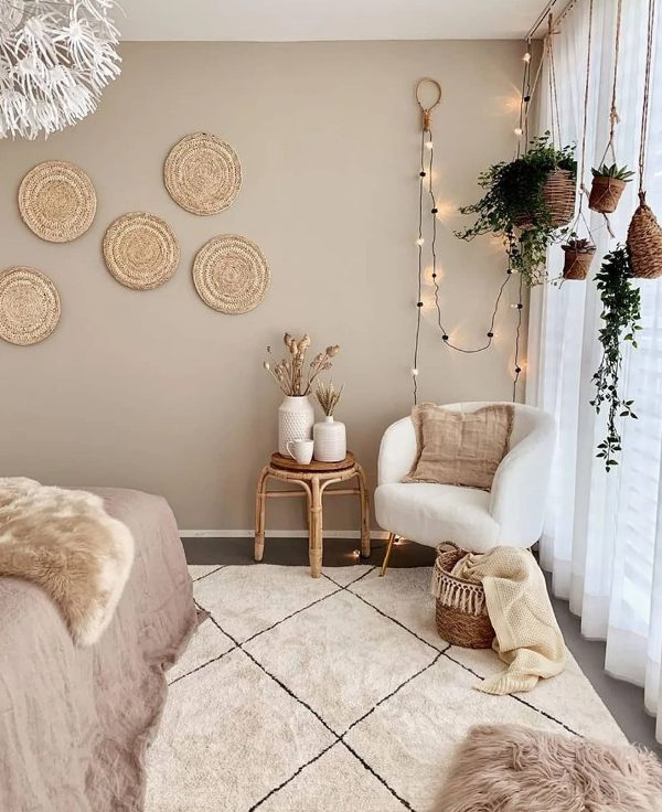a boho bedroom with taupe walls, a bed, a creamy chair, a rattan stool, hanging potted greenery, decorative woven plates and layered rugs