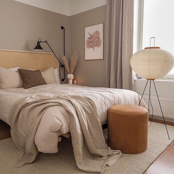 a boho taupe bedroom with a rattan bed, neutral bedding, an orange leather stool, a floor lamp and some art and pampas grass