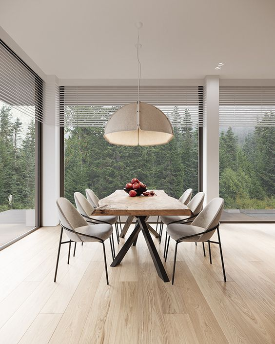 a bold contemporary dining nook with fantastic views of the forest, a living edge table, neutral rounded chairs and a pendant lamp