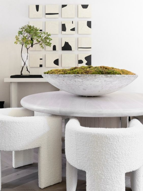 a bold contemporary dining room with a neutral console and a catchy artwork, a round stone table, creamy rounded chairs and a bowl with moss