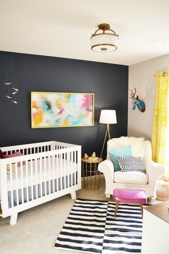 a bold nursery with a black accent wall, a striped rug and printed pillows, a pink stool and a bright artwork plus faux taxidermy is amazing