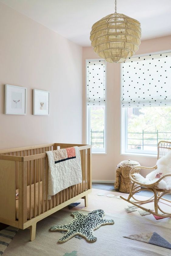 a catchy contemporary nursery with blush walls, stained wood and rattan furniture, a pendant lamp, layered rugs and polka dot shades