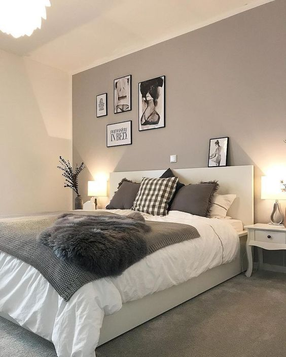 a catchy modern bedroom with a taupe accent wall, a creamy bed with taupe and white bedding, a small gallery wall
