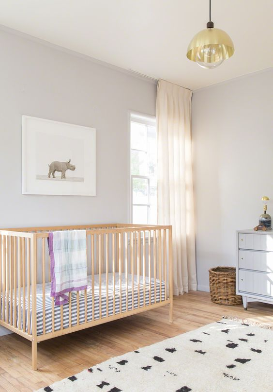 a chic and serene nursery with dove grey walls, a light-stained crib, a grey dresser, a printed rug and blanket, a gold pendant lamp