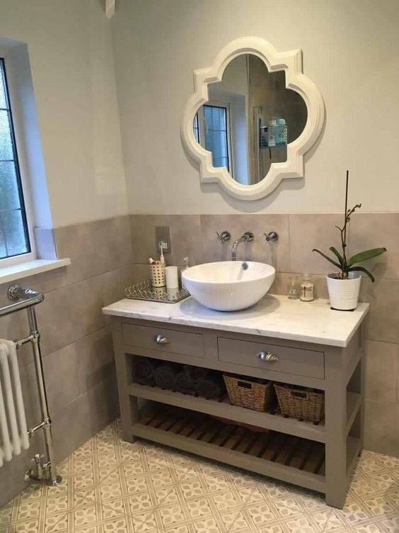 a chic bathroom with taupe and patterned tiles, a taupe vanity, a mirror in a refined frame, a bowl sink and a potted bloom is cool