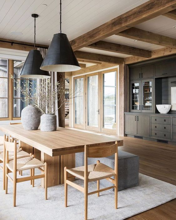 a chic contemporary dining room with a light-stained table, chairs with woven seats, black pendant lamps and a grey bench