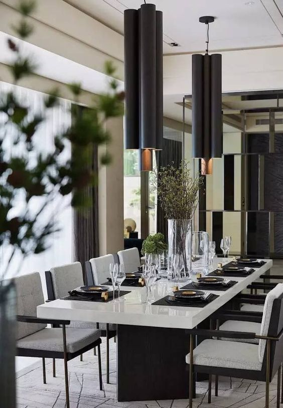 a chic contemporary dining space with a white table with black legs, black chairs with white upholstery, black pendant lamps and greenery