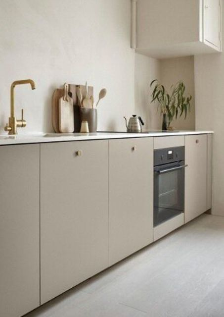 a chic contemporary kitchen with only lower cabinets in taupe, with bolg knobs and fixtures, with white stone countertops and a single white upper cabinet