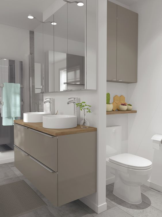 a chic minimalist bathroom in white, with a sleek taupe floating vanity and a cabinet over the toilet, mirror cabinets and white appliances