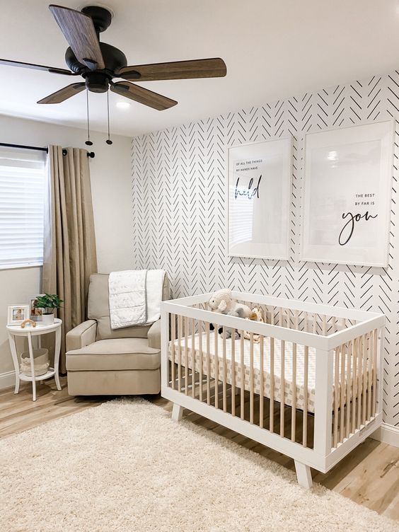 a chic modern nursery with a print accent wall, a grey chair and a white crib, a neutral rug, grey curtains and a wooden gfan plus some prints