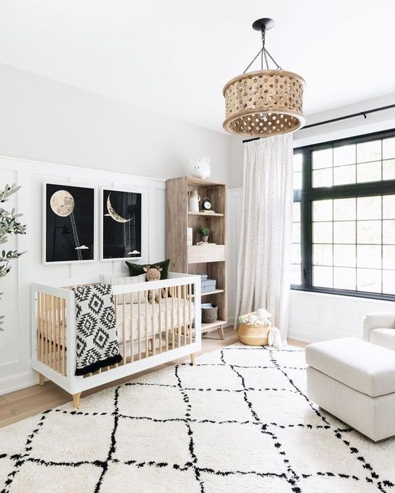 a chic modern nurseyr in black and white, with a black framed window, a stained crib, a stained storage unit, a creamy chair, printed textiles and a wooden pendant lamp