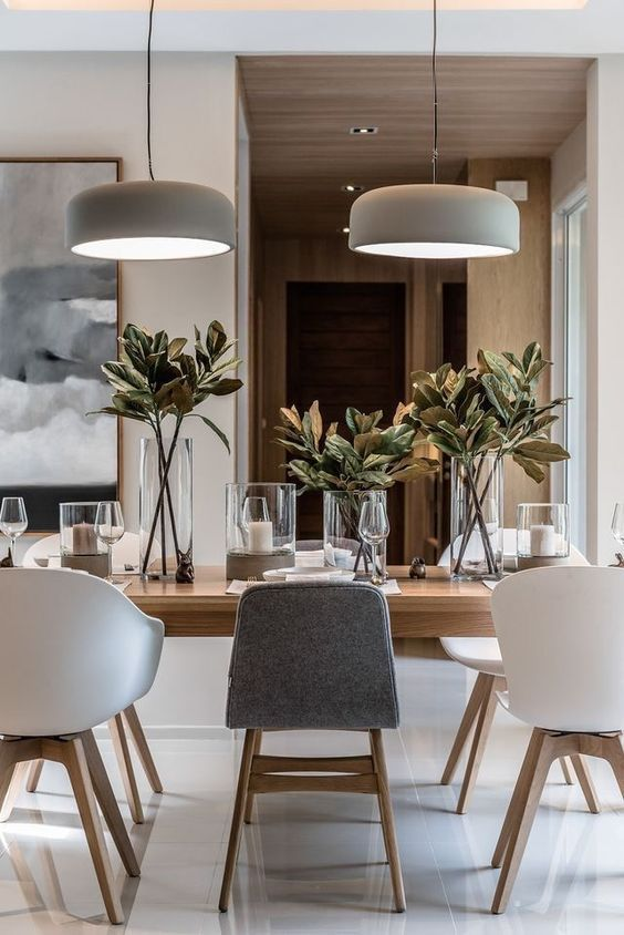 a chic neutral contemporary dining room with a light-stained table, white and grey chairs, pendant lamps, candles and foliage