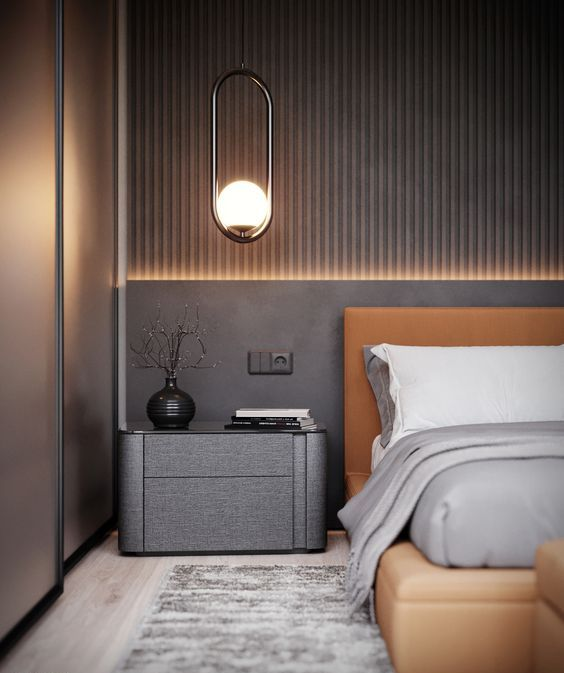 a chic taupe bedroom with a slab accent wall, an amber leather bed, a dark taupe nightstand, built-in lights and pendant lamps