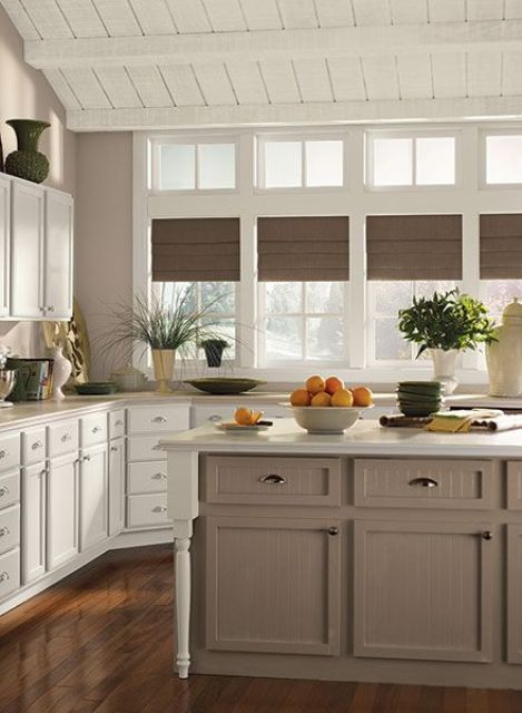 a chic vintage white kitchen with a taupe kitchen island, white stone countertops and a backsplash, taupe shades and light taupe walls