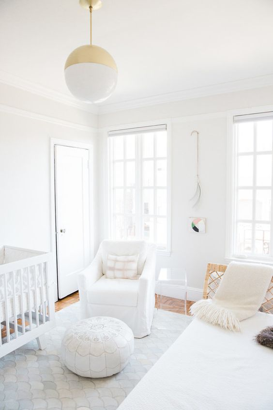 a clean white contemporary nursery with cool furniture, a Moroccan ottoman, a gold and white pendant lamp and neutral textiles