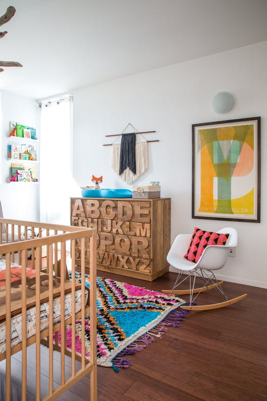 a colorful boho nursery with a stained crib and a dresser with letters carved, a white rocker, a colorful rug, bedding, colorful books on the ledges