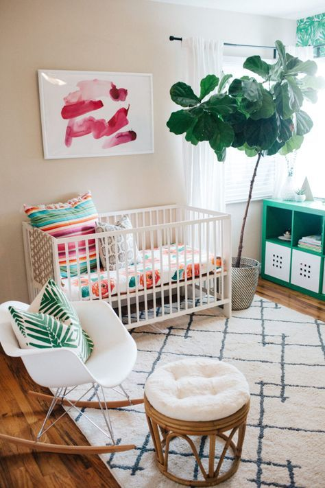a colorful contemporary nursery with a white crib, a chair, a rattan stool, an emerald sideboard, colorful bedding and an artwork