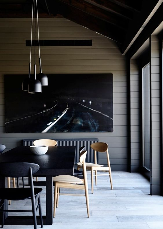 a contemporary and chic dining room with planked walls, a statement artwork, a black table, neutral and black chairs, a cluster of pendant lamps