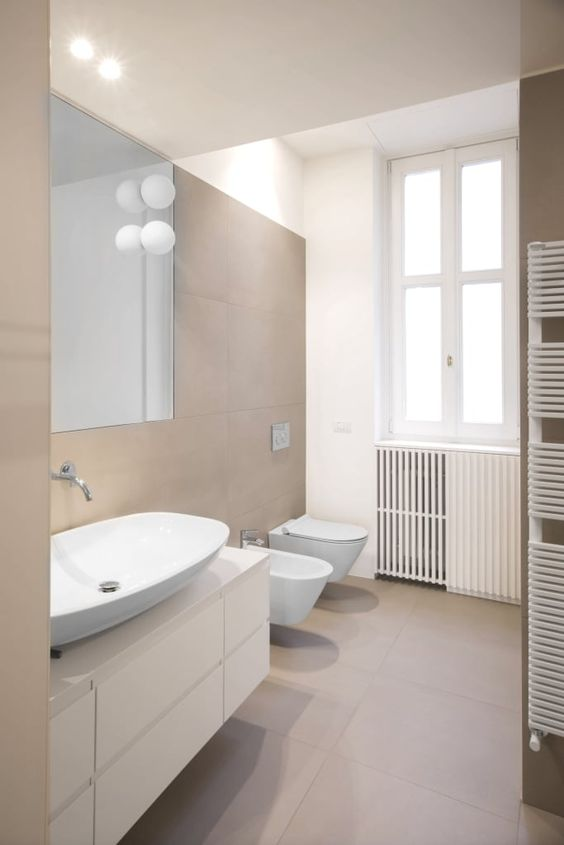 a contemporary bathroom clad with taupe tiles, a white floating vanity, white appliances and cool bubble lamps is cool