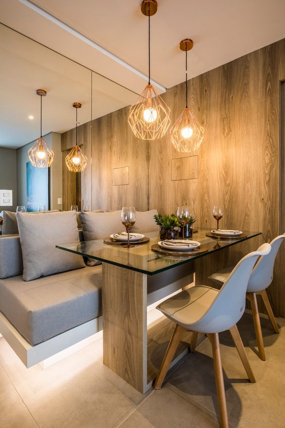 a contemporary dining nook with a mirror wall, a built-in and lit up upholstered bench, a wood and glass table and white chairs