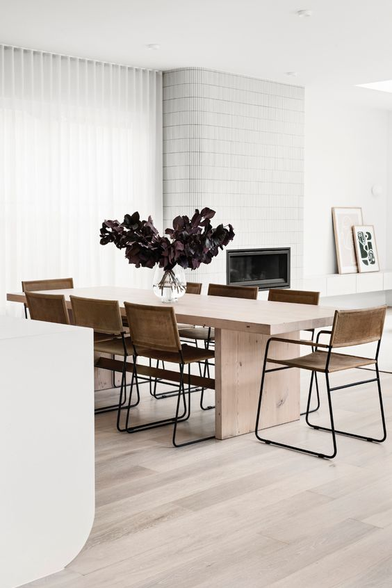 a contemporary dining room with a sleek light-stained table, leather chairs, a fireplace clad with white tiles