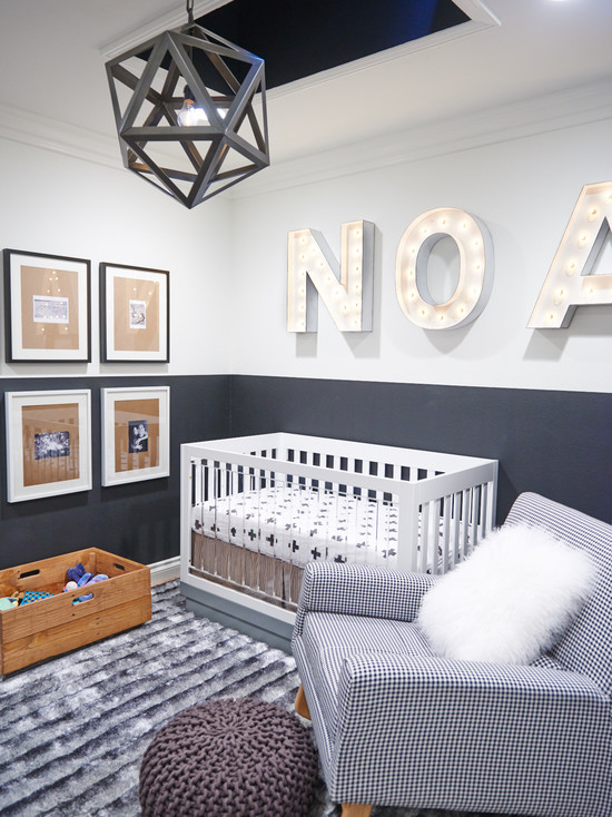 a contemporary grey and white nursery with a faceted pendant lamp, marquee letters, a mini gallery wall, a white wood and clear acrylic crib, a printed chair