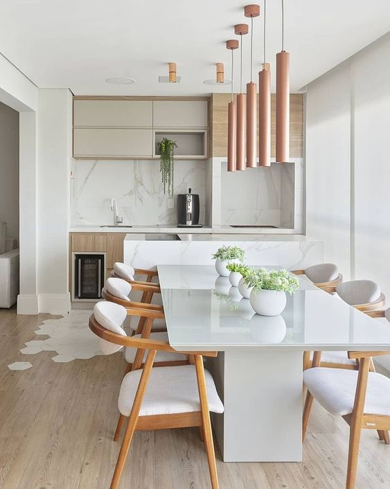 a contemporary light-filled dining room with a white stone table, white upholstered chairs, a cluster of pendant lamps and greenery