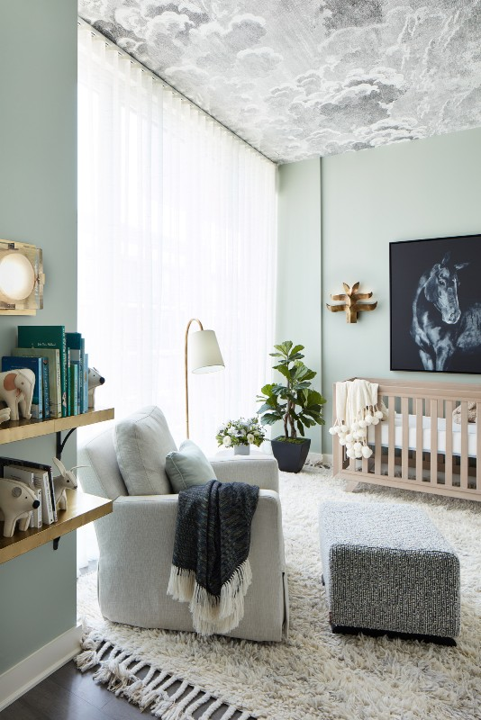 a contemporary ligth green nursery with a cloud ceiling, a neutral crib, a neutral chair with a footrest, floating shelves and potted plants