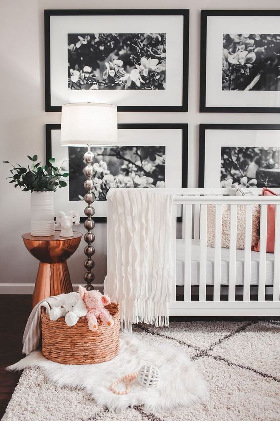 a contemporary nursery with a black and white gallery wall, a white crib, layered rugs, a basket with toys, a copper table and a floor lamp