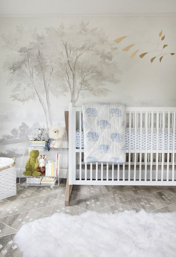 a contemporary nursery with a dreamy accent wall, white and clear acrylic furniture, layered rugs and blue bedding, cute toys