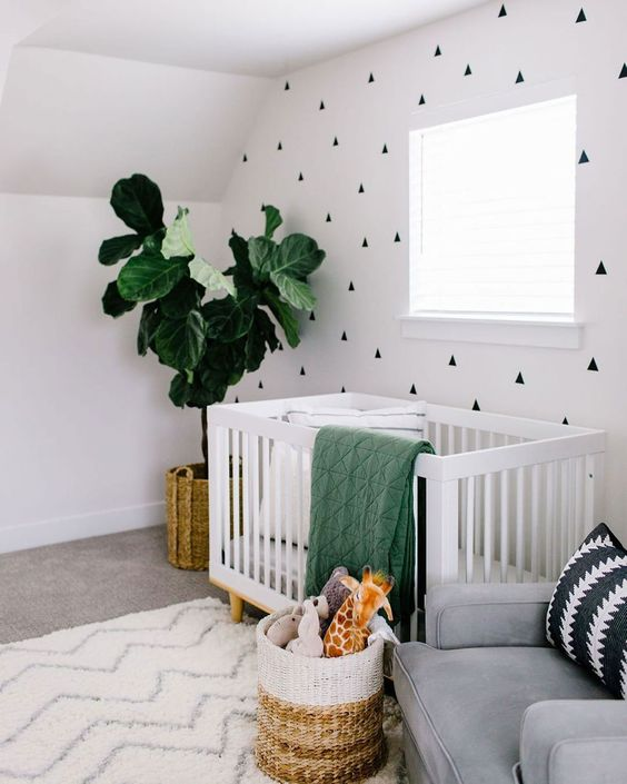 a contemporary nursery with a geo printed accent wall, a white crib, a grey chair, a potted plant, a color block basket