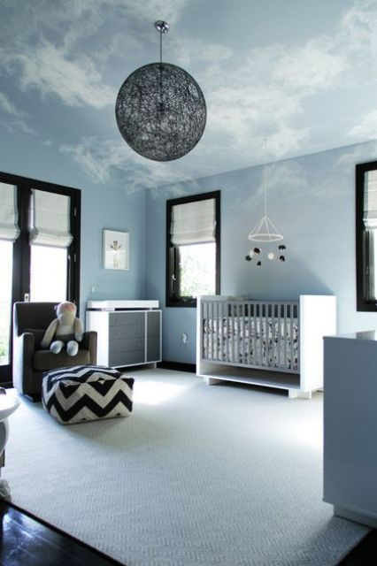 a contemporary sky blue nursery with a neutral crib and changing table, a grey chair and a printed ottoman plus a yarn ball lamp