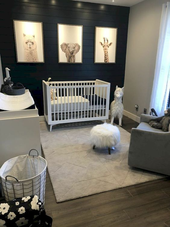 a contrasting nursery with a black plank accent wall, a white crib and changing table, a grey chair, pretty toys and a print gallery wall