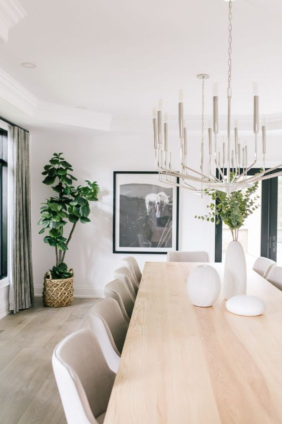 a cool contemporary dining room with a neutral dining table, creamy chairs, a statement chandelier and a bold artwork plus greenery