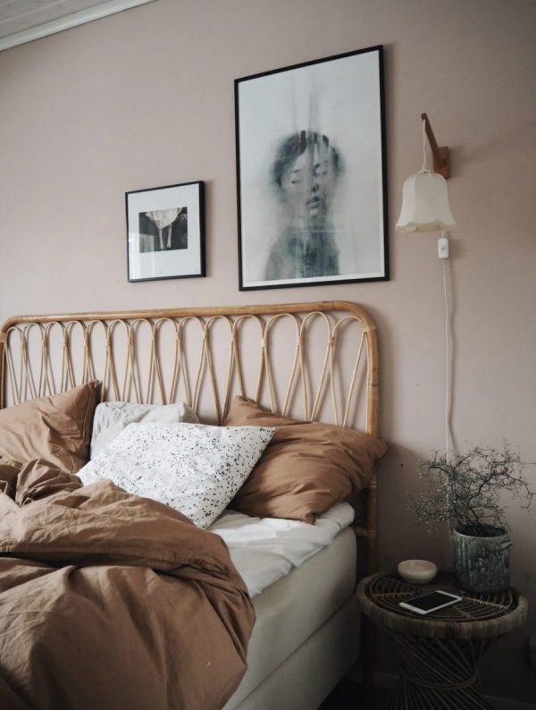 a cozy bedroom with light taupe walls, a rattan bed and a stool, a mini gallery wall and a potted plant plus sconces
