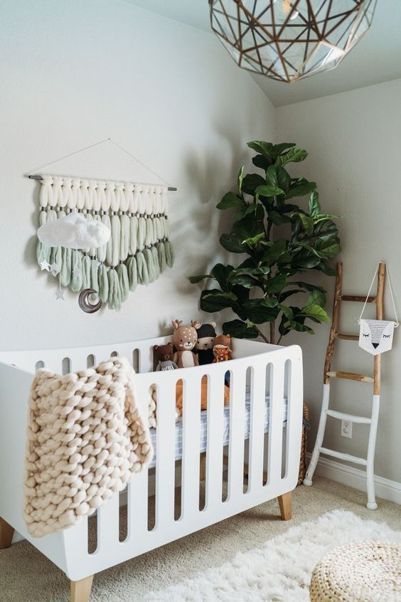 a cozy boho nrusery with a white crib, a painted ladder, some lovely boho decor, toys, poufs and a statement plant is very welcoming
