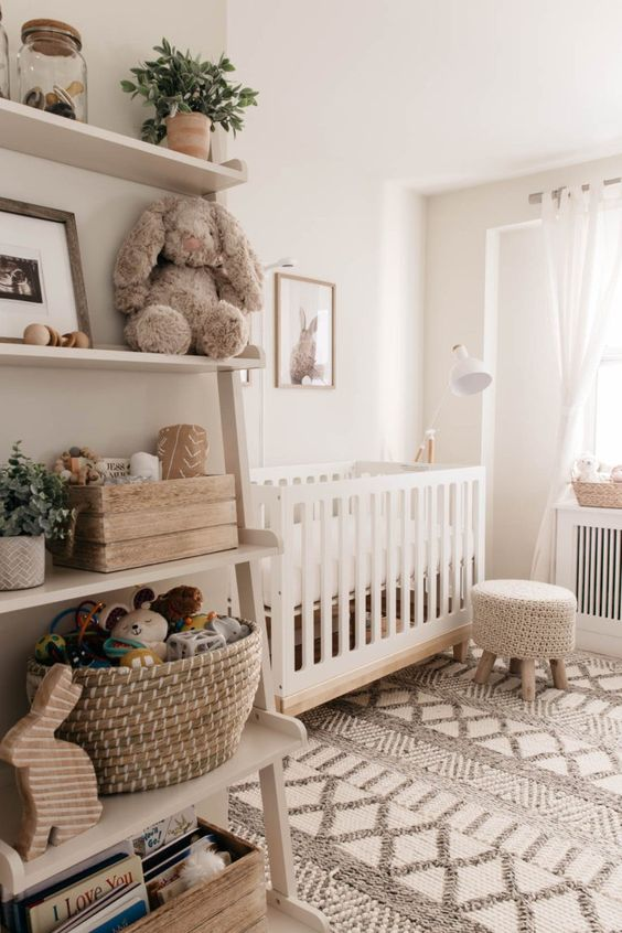 a cozy neutral nursery with a white crib, a crochet stool, a printed rug, an open shelving unit and some potted plants is cool