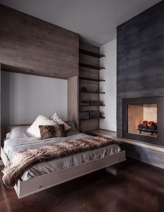 a cozy rustic bedroom with a taupe wooden accent wall, a fireplace clad with black wooden plants, a hidden bed and built-in shelves