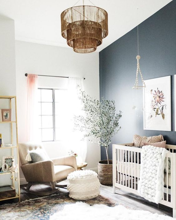 a delicate and cool contemporary nursery with a black accent wall, a white crib, a tan rocker chair, an open shelving unit, a fringe chandelier and a tree
