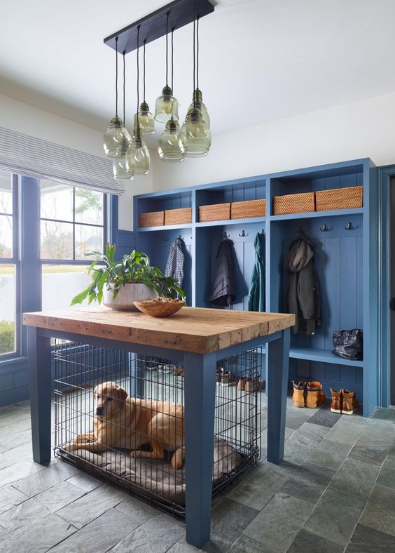a farmhouse entryway with a blue clothes rack with seats, blue walls and a matching dog kennel with a butcherblock countertop